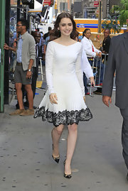Lily looked like the girl next door when she wore this long-sleeve white dress with black lace detailing at the hem.