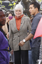 Linda Evans went for a classic look with a gray tweed jacket over a rust-hued blouse.