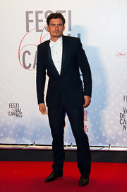 Orlando Bloom chose a modern navy tux with a solid white button down and matching tie for his look at the premiere of 'Zulu.'