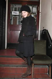 Elisabeth Moss bundled up in ondon in a pair of brown suede motorcycle boots.