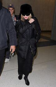 Madonna wore a black fur earflap cap to the JFK airport with her warm ensemble.
