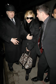Madge stepped out for a bite to eat in a bundled up ensemble carrying a printed leather tote. The brown handbag featured two zip-top closures and double-strapped handles.
