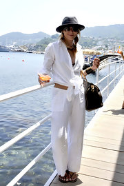 Maria Bello embraces summer style by creating an off-duty summer suit by pairing a knotted button-down with breezy wide-leg pants.