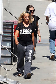 "Lacey wears a v-neck black t-shirt with multiple holes and the word ""Blessed."""