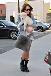 Miley is obviously a fan of fuzzy effects. She's seen here toting an adorable puppy and a grey faux-fur messenger bag. Very cute.