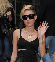 Miley Cyrus displayed an om tattoo on her wrist while waving to photographers in London.