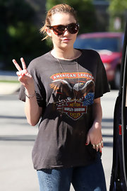 Miley Cyrus flashed a peace sign as she posed for the cameras in brown rectangle shades.