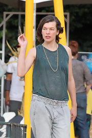 Milla Jovovich added a tiny metallic tough to her teal tank with a thin gold chain.
