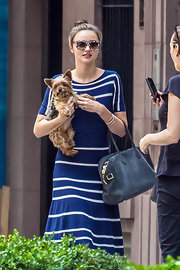 Miranda Kerr accessorized with a stylish suede bowler bag on one arm and a cute puppy on the other while strolling in NYC.
