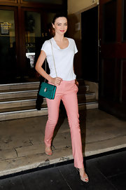 Miranda Kerr accented her girlish pink pants with a petite teal chain strap purse.