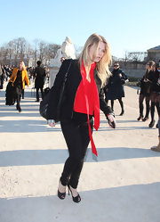 Melanie wears a red tie neck blouse with her black ensemble for Fashion Week in Paris.