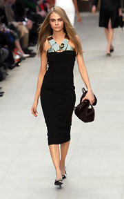 Cara Delevingne partnered her LBD with a fur purse as she walked down the LFW Burberry runway.