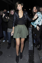 Frankie Sandford looked teeny tiny in an olive fit and flare mini skirt.