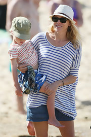 Naomi matches her son at the beach in a striped t-shirt.