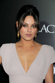 Mila Kunis added an elegant touch to her plunging neckline with a classic French twist complete with face framing bangs.