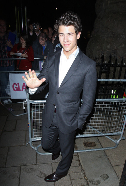 Nick opted to forgo a tie and unbuttoned his neckline with a tailored gray suit.