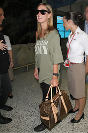 Nicky Hilton paired her army green shirt with a printed brown tote bag.