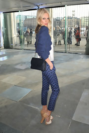Poppy Delevigne accented her playful polka dot pants and tweed jacket with a ladylike black quilted bag.
