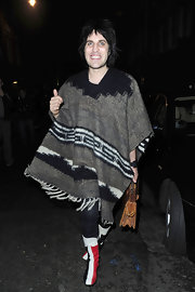 Noel wears funky striped boots with a poncho and leather purse.