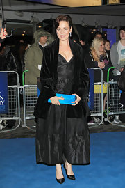 Olivia Colman wisely broke up her all black look with a vibrant robins egg blue clutch.