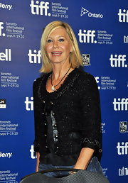 Olivia Newton-John donned a stylish tweed jacket at at a press conference.