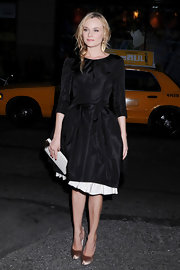 Diane Kruger accented her black silk frock with a nude ivory kiss lock clutch.