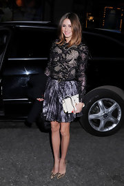 Olivia Palermo added contrast to her detailed look with a sleek cream clutch with gold accents.