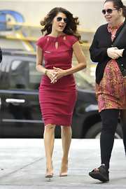 Marisa wore a form-fitting raspberry red sheath dress with a cutout neckline and nude pumps.