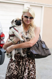 Paris showed off her brown leather tote bag while doing some shopping with her new pet pug.