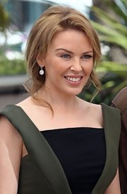 Kylie Minogue arrived at a photocall for 'Holy Motors' with her hair styled in a low ponytail with lots of loose wavy tendrils.