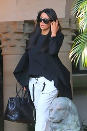 Kim Kardashian toted a black crocodile bag during a trip to Miami.