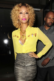 Keri donned a bold yellow button-down blouse with dramatic cut-outs while out for dinner in London.