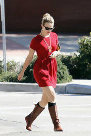 Rachel McAdams transitioned her summery red dress into her fall look with the addition of flat leather boots.