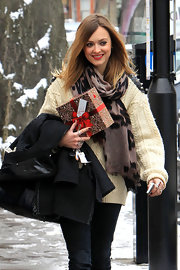Fearne wears a thick woven scarf with a black and maroon print pattern.