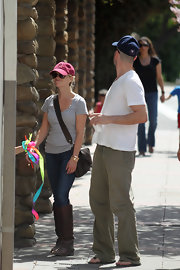 Reese carried a cross body brown leather messenger bag while out for a walk. These convenient bags have plenty of space keep her hands free to hold onto her cute new beau Jim.