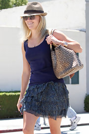 Reese paired her ruffled skirt with a straw fedora hat and a woven shoulder bag.