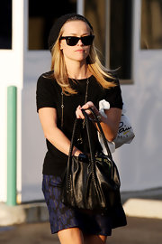 Reese looks very stylish shopping in Westwood. She has on a trendy cable beanie. She completes her outfit with black wayfarer shades.