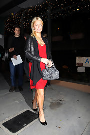 Paris Hilton carried a flashy black tote with crystal swirls while dining out with family.