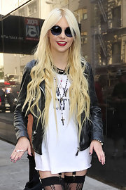 Taylor layered pearls, with a black rosary and two pendant necklaces to accessorize her bold ensemble.