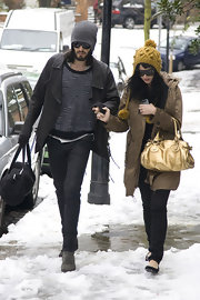 "On a snowy day newly engaged couple Katy Perry and Russell Brand make their way out of Rusell's home. Even in the snow Katy remians stylish with her gold metallic ""Paddington"" bag by Chloe."
