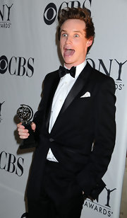 Eddie looks jubilant holding his Tony Award in a dashing black tuxedo.