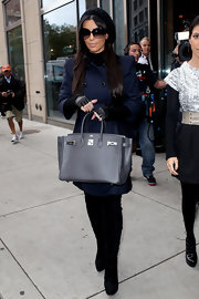 When Kim Kardashian pauses for a pic, her Birkin bag often gets pride of place. Here she shows of a new black model with silver hardware.