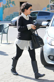 Kourtney Kardashian wore black flat leather boots.