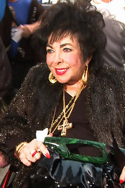 Elizabeth Taylor piled on the jewels, among them a huge gold cross pendant necklace.