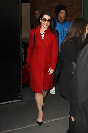 Kristin Davis as a vision in a red wool coat with retro pearly buttons.