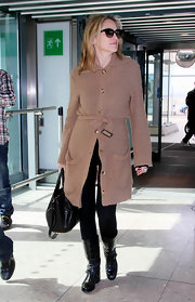 Sharin wore a long slouchy camel cardigan to the airport with her black ensemble.