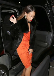 Rihanna showed her glamorous side with a black fur coat paired with an orange cocktail dress.