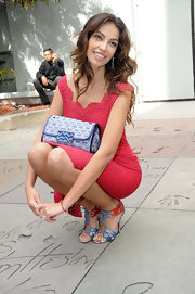 Madalina Ghenea added some funky flair to her red dress with a purple printed clutch while out in LA.