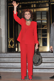 Sophia Lauren looked ravishing in a red pantsuit. She added a European touch with a scarf tied around her neck.