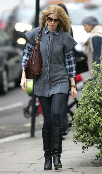 Claudia dons a short sleeve cable knit sweater over a plaid button-up while out in London.